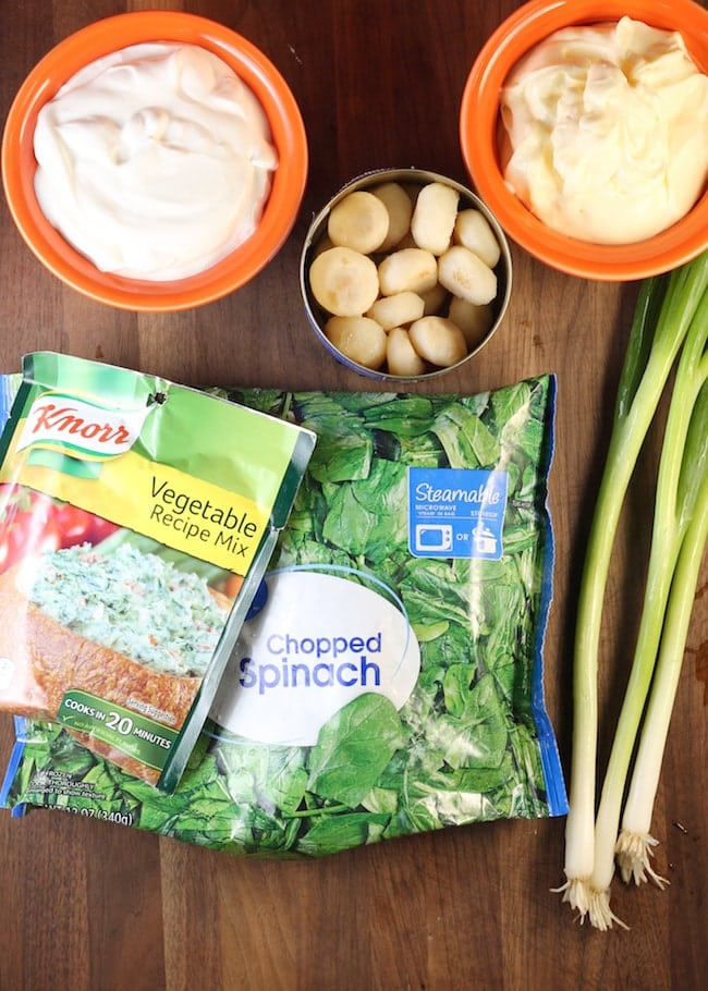 Ingredients for Knorr Spinach Dip - Knorr Vegetable Mix, Frozen Spinach, Green Onions, small bowl of sour cream, open can of water chestnuts and small bowl of mayonnaise