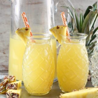 Glass Pitcher and Pineapple Shaped Glasses filled with Easy Pineapple Wine Punch with pineapple top and pineapple wedges