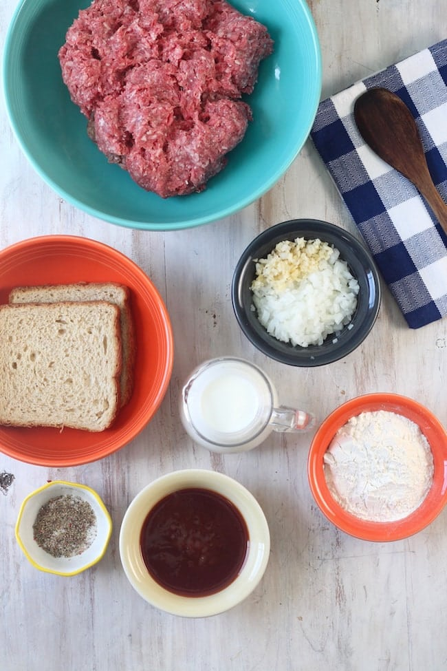 2 slices of wheat bread, ground beef in a blue bowl, chopped onions and garlic in a bowl, milk in a clear pitcher, flour in a bowl, barbecue sauce in a bowl, salt and pepper in a bowl, blue check napkin with a wood spoon laying on it ~ Ingredients for Barbecue Meatballs