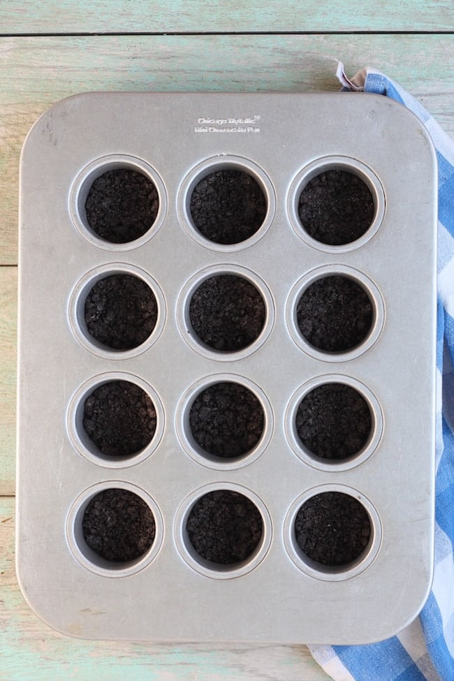 Oreo Crust in mini cheesecake pan for Mini Cherry Cheesecakes Recipe