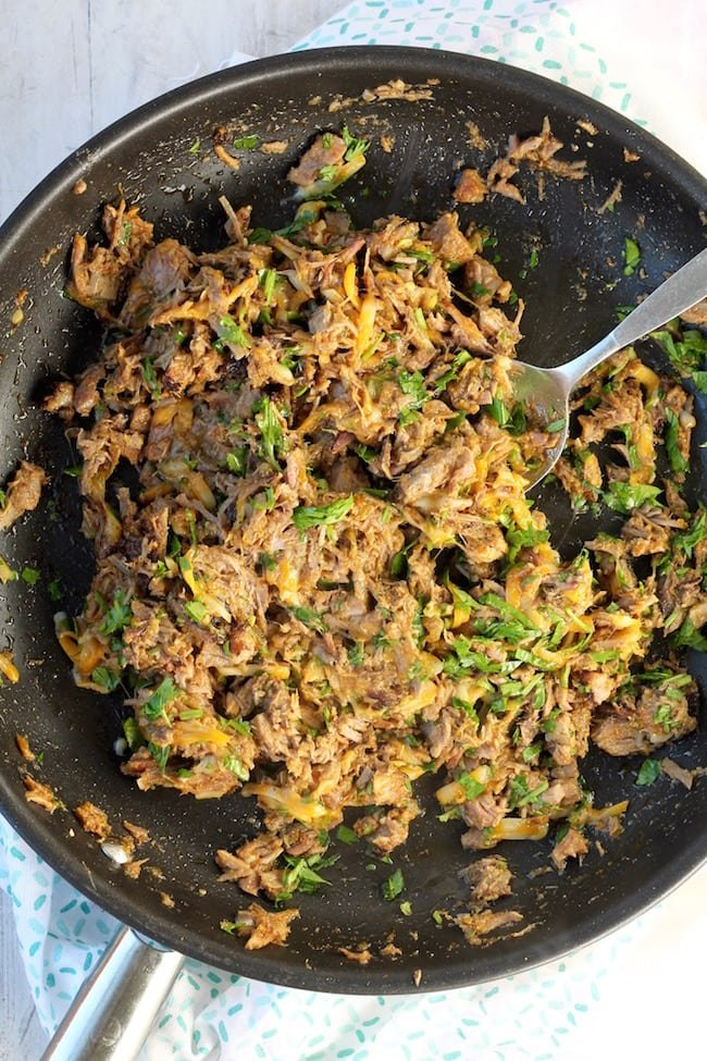 Skillet with shredded brisket, salsa verde and cheese for brisket taquitos