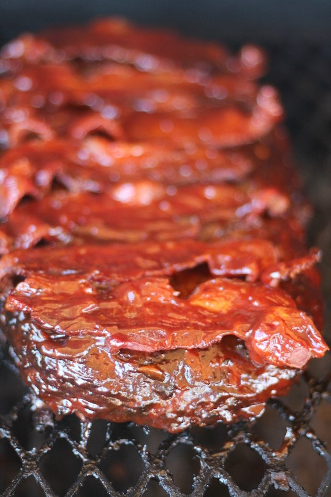 Classic Meatloaf topped with barbecue sauce and bacon on the grill for the best smoked meatloaf
