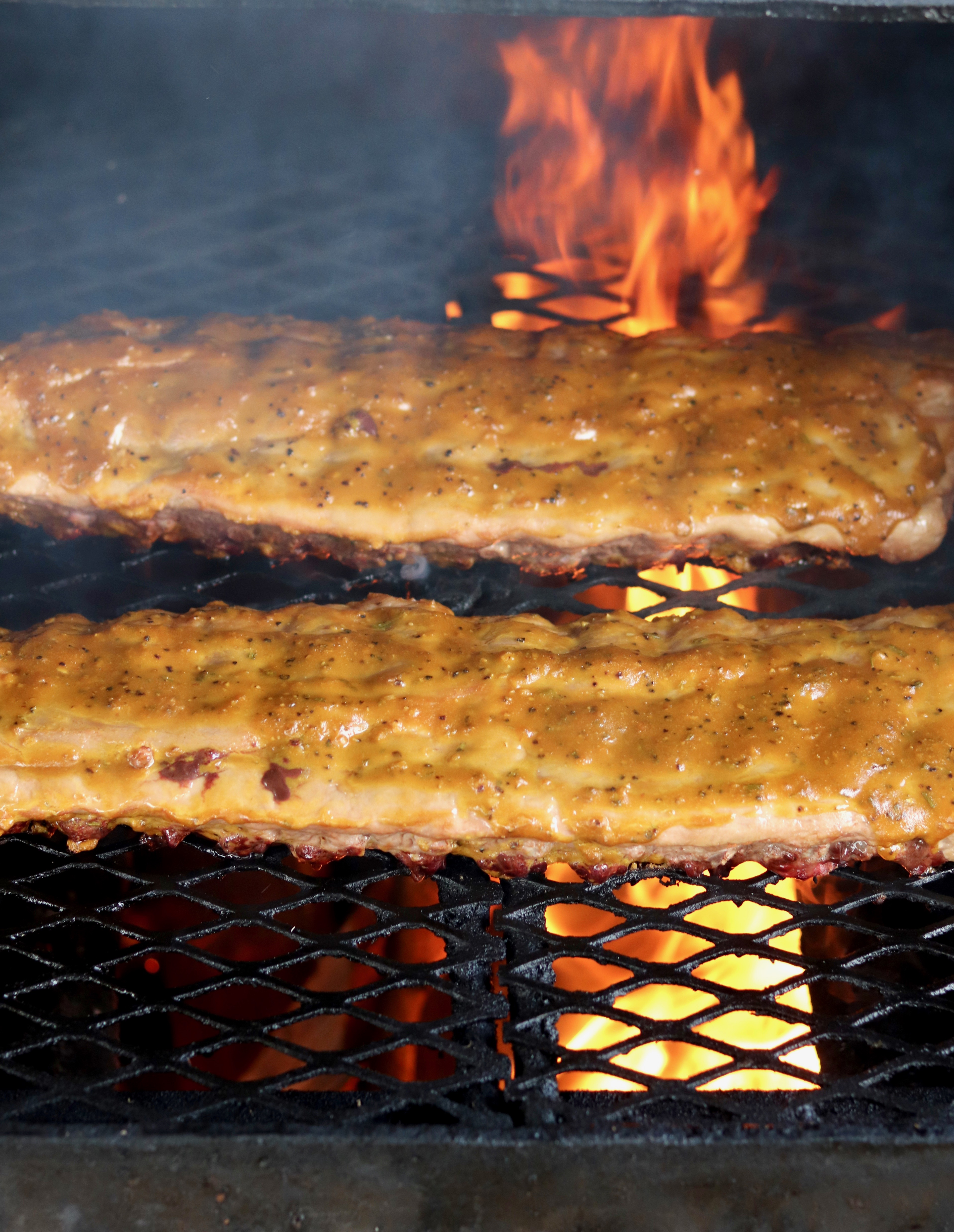 Baby Back Ribs on grill with fire in background